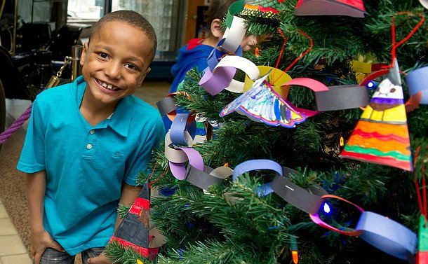 A child smiling with his teeth showing, standing next to a decorated Christmas tree.