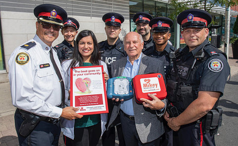 A group of people most in TPS uniform standing with a defibrillator