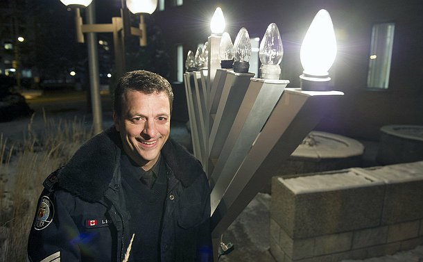 Police officer standing in front of an electrical menorah, with two candles lit up.