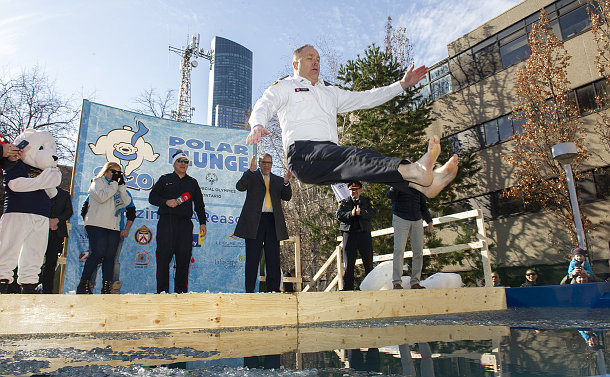 A man in police uniform jumps in a pool