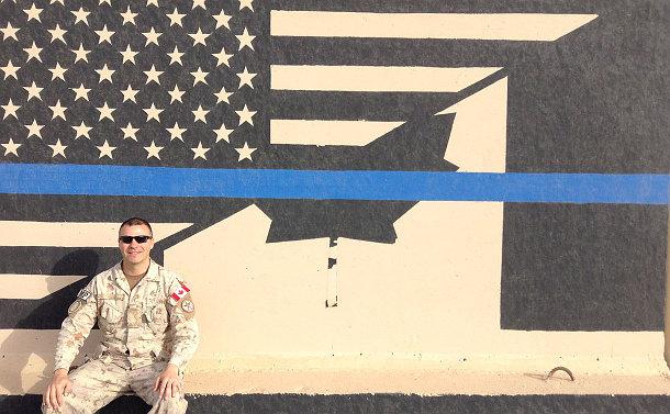 A man beside a U.S. Canada flag mural on a wall