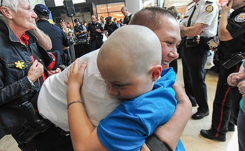 A woman with a shaved head is hugged by a boy with a shaved head