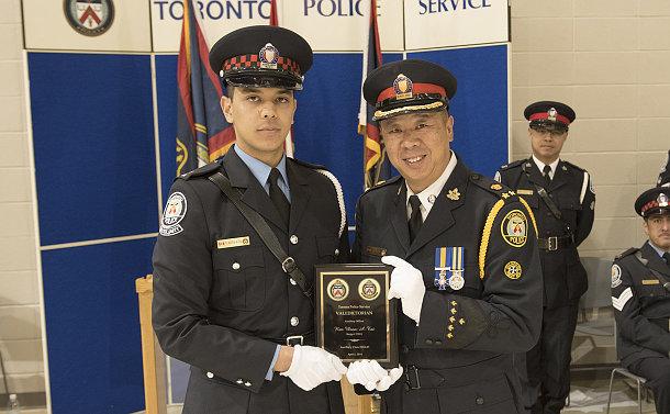 Two men in TPS uniform holding a plaque