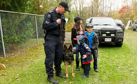 A young boy next to a dog with a police officer holding on to it with a leash. Two other older children look at the dog.