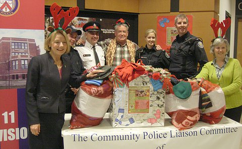 A group of seven men and women, three in Toronto police uniform behind and beside a table with bags of clothing on it