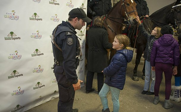 A man in TPS uniform speaks to a girl near horses