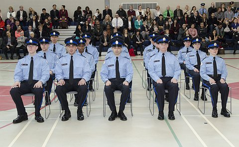 A group of men and women in TPS court officer uniform seated in front of an audience