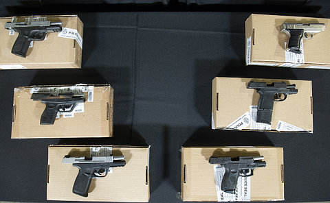 A table of handguns on boxes
