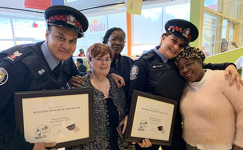 Two uniformed TPS members holding certificates with women