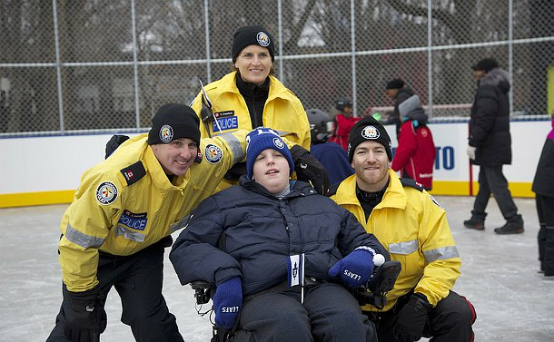 A man in a wheelchair with two men and one woman in TPS uniform around him on a skating rink