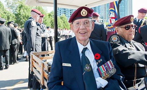 A man wearing a Toronto Police Military Veteran beret and medals smiles for the camera.