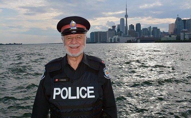 Man in a police uniform with a panorama of a lake and cityscape in the background