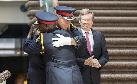 Two men in TPS uniform hug