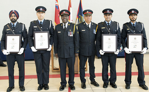 Six men in uniforms, some holding award plaques