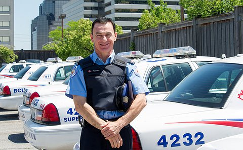 A man in a TPS parking uniform stands beside police scout cars
