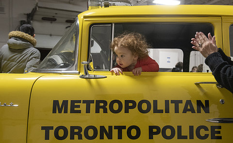 A child looking out a yellow police car window