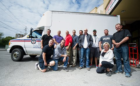 A group of men and women standing and kneeling in front of a TPS cargo truck