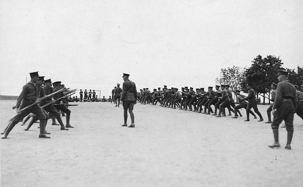 A group of men in uniform in two lines with rifles