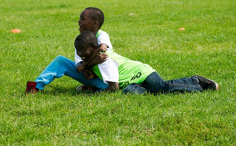 Two young boys on the grass, with one hugging the other.