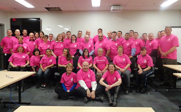 A large group of men and women wearing pink T-shirts