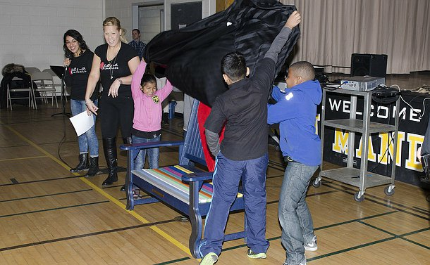 Several children pull a black tarp from a bench