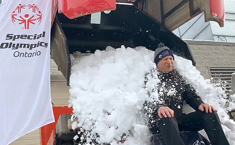 A man in TPS uniform has snow dumped on him from a Zamboni