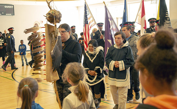 Man carrying a staff with eagle feathers is followed by a elderly woman and a young boy, who are followed by a group of men and women carrying flags of various nations