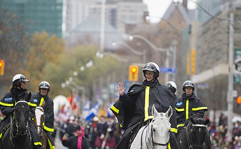 A woman in uniform on horseback waving to onlookers