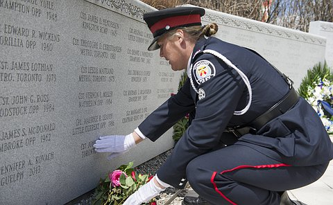 A women in TPS uniform crouches and touches a memorial wall where flowers are laid