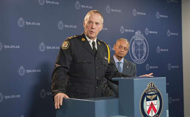 A man in TPS uniform in front of a podium with another man
