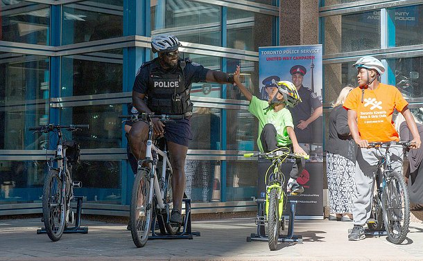 A man in TPS uniform high-fives a child, both on bikes