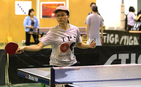 A woman swings at a ball in mid flight with a table tennis racket at a table