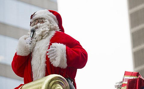 A man in a Santa Claus costume atop a sleigh