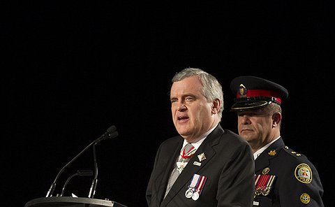 A man in a business suit with medals on his chest stands at a podium speaking while another man in a Toronto Police uniform stands behind him