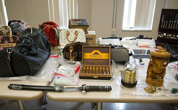 Items on a table including a sword, jewellery, purses and other valuables.
