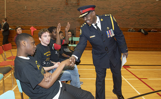 A man in TPS uniform shaking hands with a youth