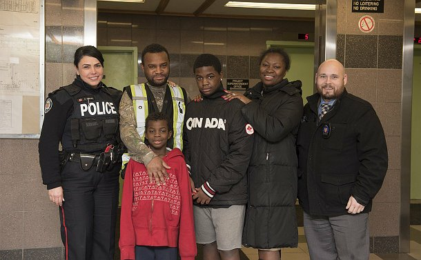 A woman in police uniform with two other men, a woman and two boys in an apartment lobby