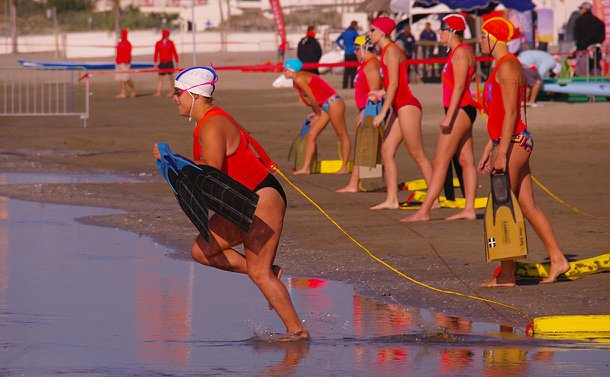 A woman holding flippers runs toward the water with a life preserver in tow