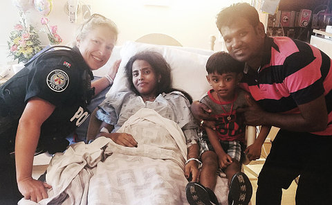 A woman in TPS uniform with a woman in a hospital bed and a man and boy