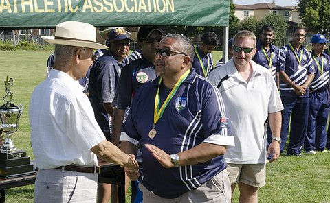 Two men shake hands, one wears a medal