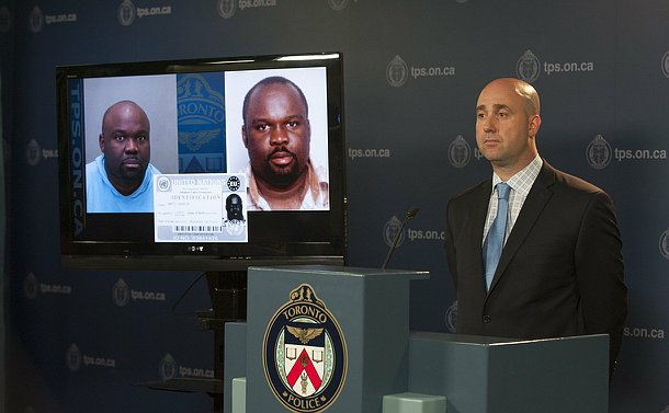 A man stands at a podium beside a TV with photos of another man
