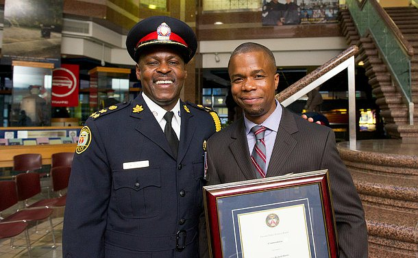 A man in TPS uniform with another man holding a framed certificate