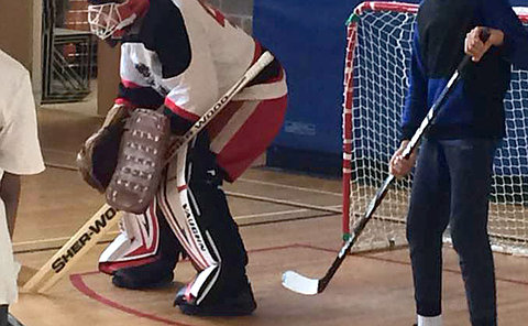 A man in goalie equipment and a boy holding a hockey stick