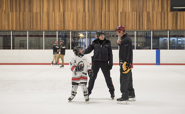 A boy in hockey uniform, a woman in police uniform and a man on a rink