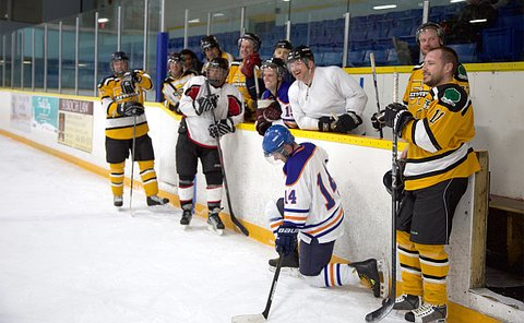 A group of men in hockey uniform in and around a team bench