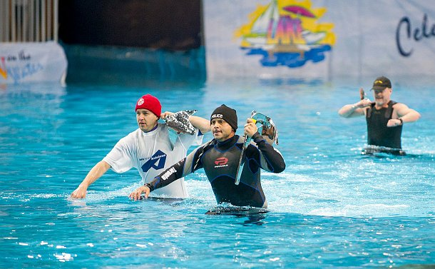 Two  men in wet suits carrying silver anchors on their shoulders run in an indoor swimming pool