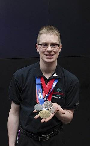 A man wearing and holding several medals