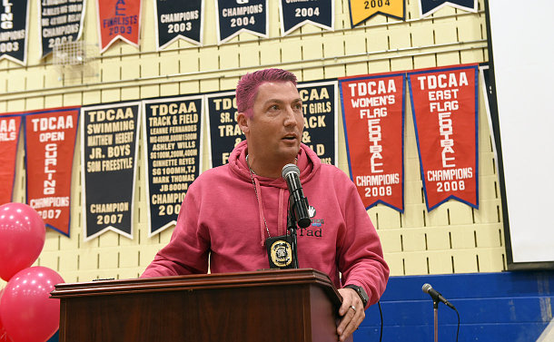 A man in a pink shirt and hair at a podium