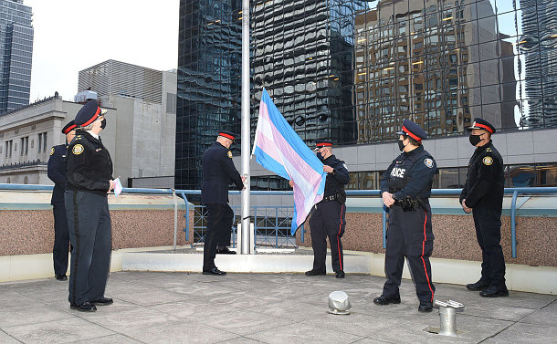 A group of police officers around flagpole