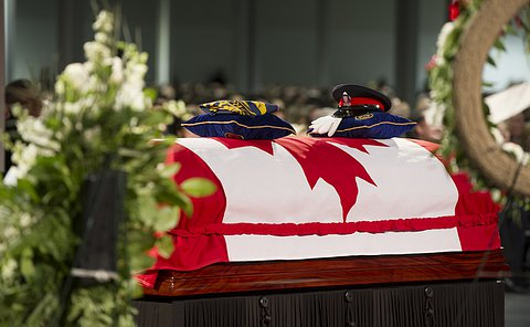 A flag draped casket with items on top of pillows